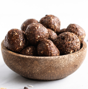 A coconut shell bowl filled with little energy balls aka low FODMAP peanut butter brownie bites.
