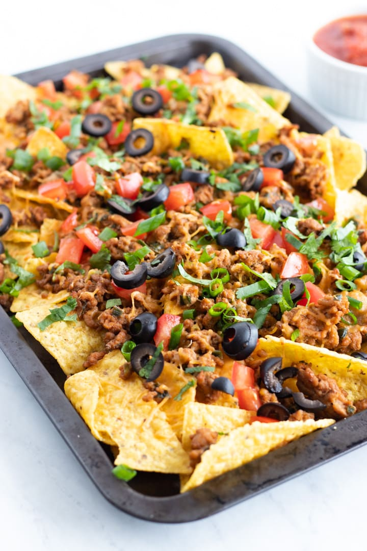 A rimmed baking sheet filled with low FODMAP sheet pan nachos. There's a small white bowl in the background filled with low FODMAP salsa.