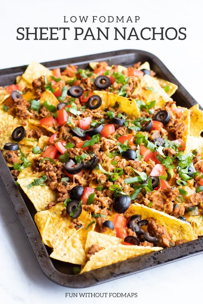 A close up of low FODMAP sheet pan nachos or corn chips topped with sliced black olives, diced fresh tomatoes, cilantro, ground turkey, green onion tops, and melty cheddar. Dark gray text at the top of the image reads Low FODMAP Sheet Pan Nachos. At the bottom it also says FUN WITHOUT FODMAPS.