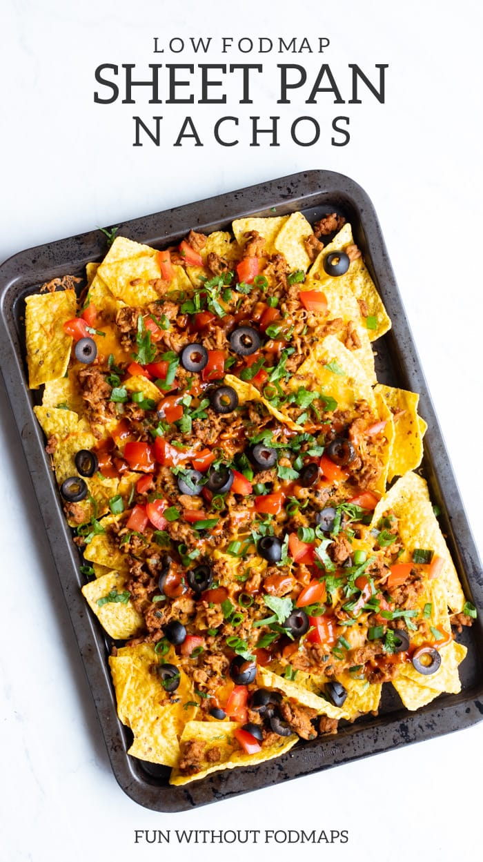An overhead shot of rimmed baking sheet filled with low FODMAP sheet pan nachos sits on white marble slab. There is dark gray text at the top and bottom that reads low FODMAP sheet pan nachos and FUN WITHOUT FODMAPS.