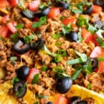 A close up of low FODMAP sheet pan nachos or corn chips topped with sliced black olives, diced fresh tomatoes, cilantro, ground turkey, green onion tops, and melty cheddar.
