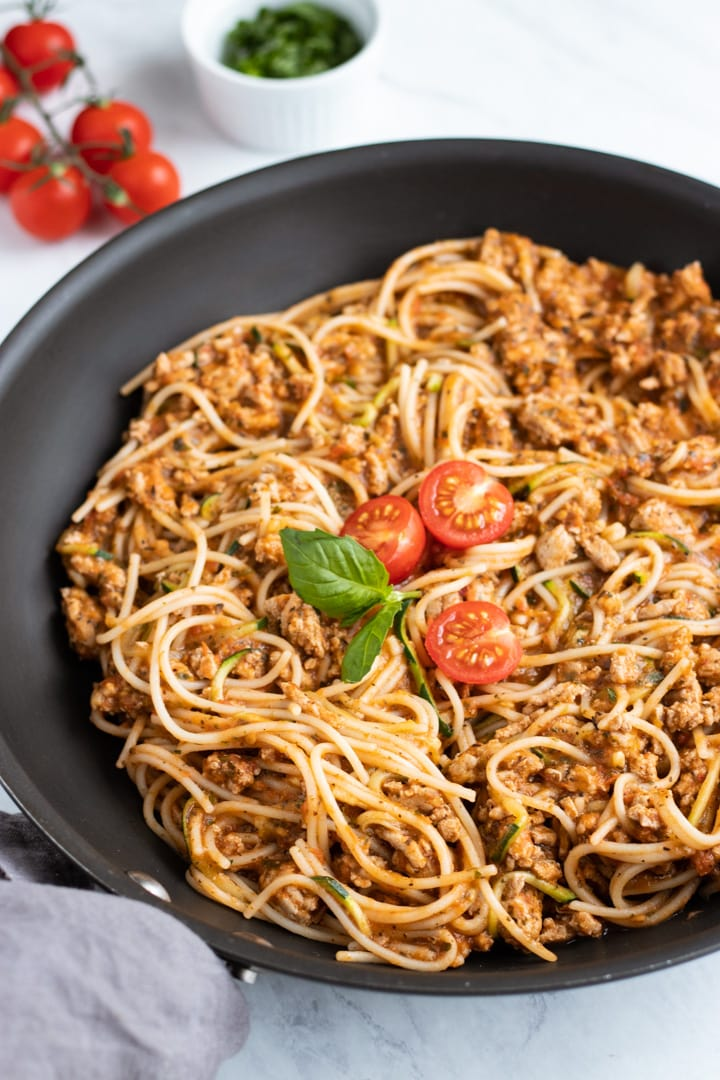 A black skillet is filled with low FODMAP spaghetti and zoodles. Three cherry tomato halves and a couple of basil leaves are artistically placed in the center of the skillet.