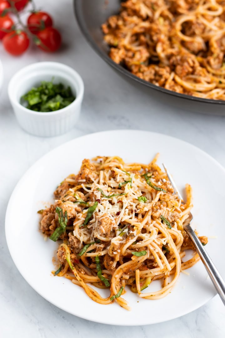 A white plate filled with low FODMAP spaghetti and zoodles sits on a white marble slab. There is a fork set on the plate. A skillet filled with additional pasta, a couple of cherry tomatoes, and a dish filled with shredded basil fill the background.