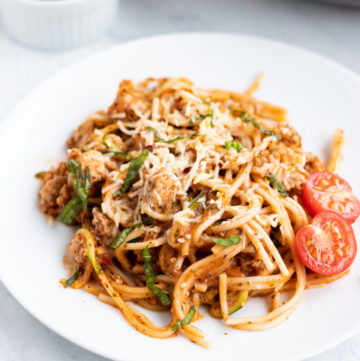 A close up of a white plate filled with low FODMAP spaghetti and zoodles