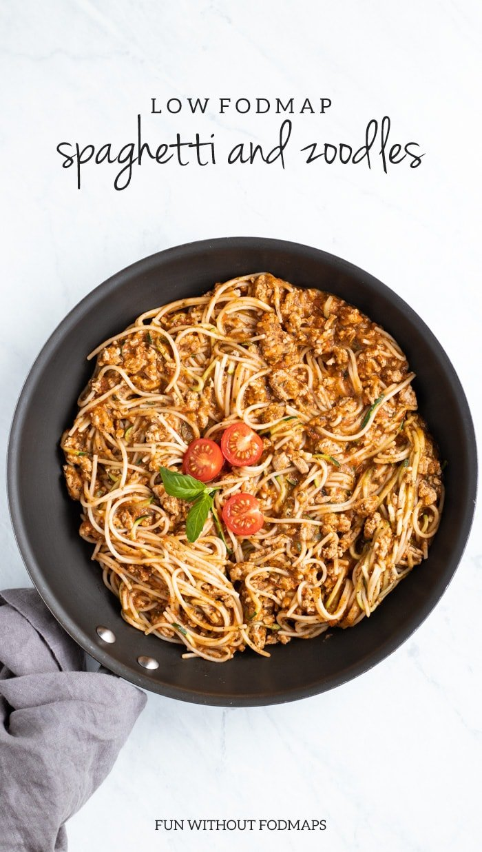 An overhead shot of a skillet sitting on a white marble slab. The skillet is filled with cooked spaghetti and topped with a couple of cherry tomato halves. The skillet's handle is wrapped in a dark gray napkin. At the top of the image, dark gray text reads low FODMAP spaghetti and zoodles and FUN WITHOUT FODMAPS is centered at the bottom.