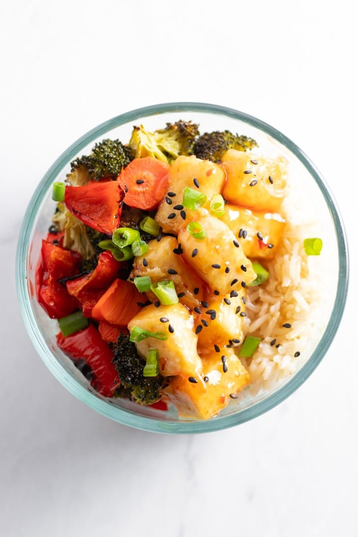 An overhead shot of a single round pyrex filled with baked tofu, roasted broccoli, red bell pepper, carrots, and whole grain rice, also known as low FODMAP sweet chili tofu bowls