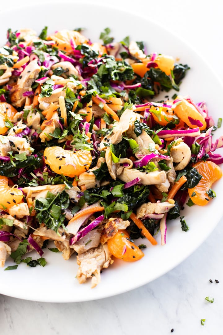 A plate of Chinese chicken salad filled with colorful kale, red cabbage, carrots, mandarin oranges, green onion tops, and chicken.