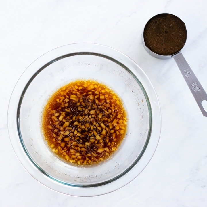 A bowl filled with sesame ginger dressing and a measuring cup with marinade