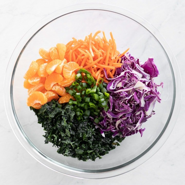Bowl of shredded cabbage, kale, carrots, green onion tops, and mandarin orange segments