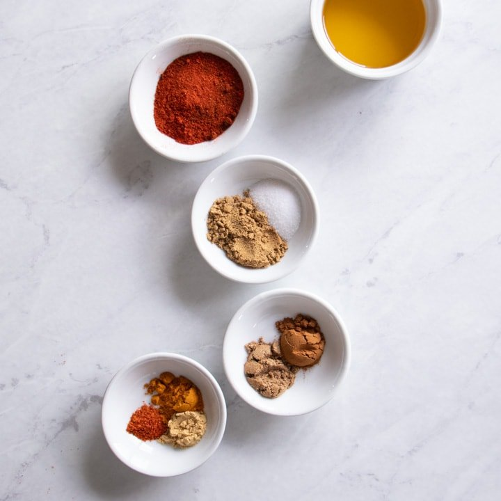 Small white containers filled with spices needed to make Low FODMAP Moroccan Chicken
