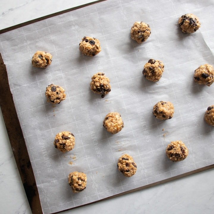 Cookie dough rolled into balls and placed on a baking sheet lined with parchment paper.