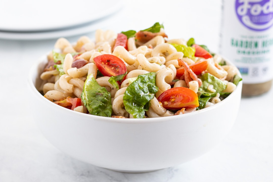 A bowl of low FODMAP BLT pasta salad made with cooked brown rice noodles, cherry tomatoes, romaine, bacon crumbles, and bottled low FODMAP dressing