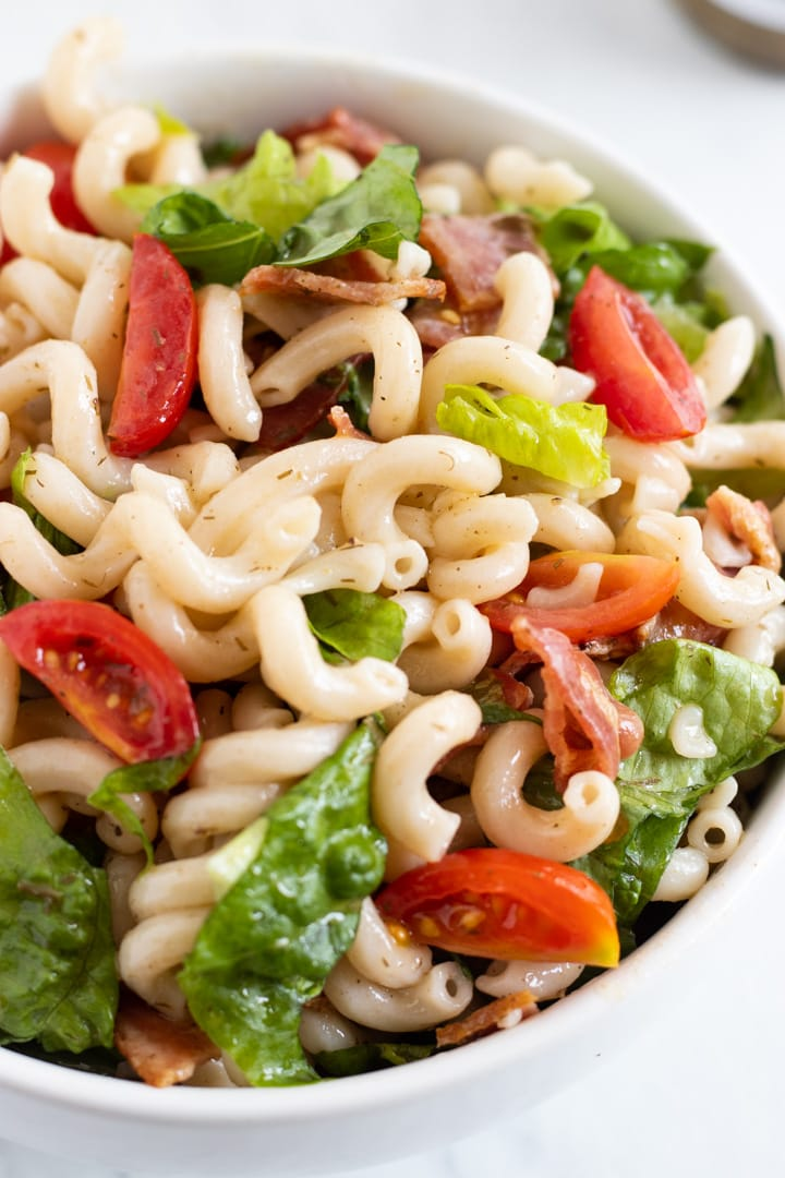 A close up of a salad made with cooked brown rice pasta, romaine lettuce, crumbled bacon, quartered cherry tomatoes, and Fody Foods Garden Herb Dressing