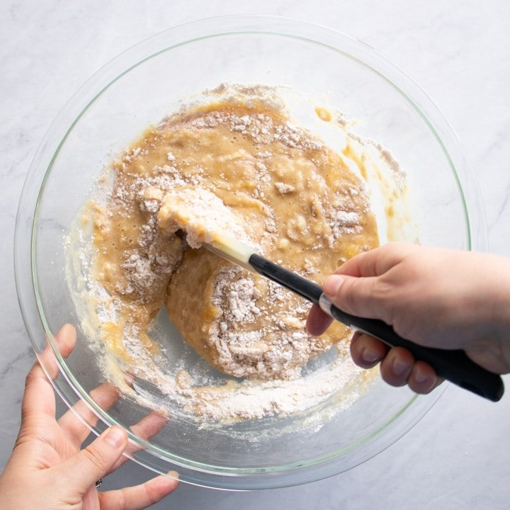 Mixing dry bread ingredients into a bowl of wet ingredients.