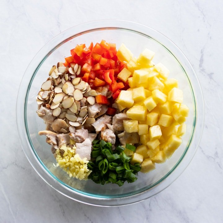 A glass mixing bowl containing the main ingredients for Hawaiian chicken salad - cooked chicken, pineapple, green onion tops, red bell pepper, sliced almonds, and fresh ginger.