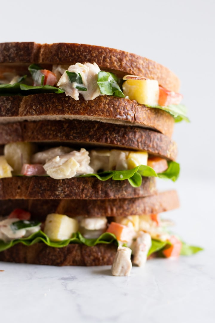 A stack of Hawaiian chicken salad sandwiches containing a chicken salad made with chicken, pineapple, and red bell pepper tossed in a mayonnaise-based dressing. The salad is layered with lettuce leaves on low FODMAP sourdough bread.