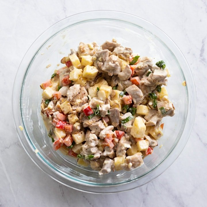 The salad dressing and chicken salad ingredients are mixed together in a large glass mixing bowl.
