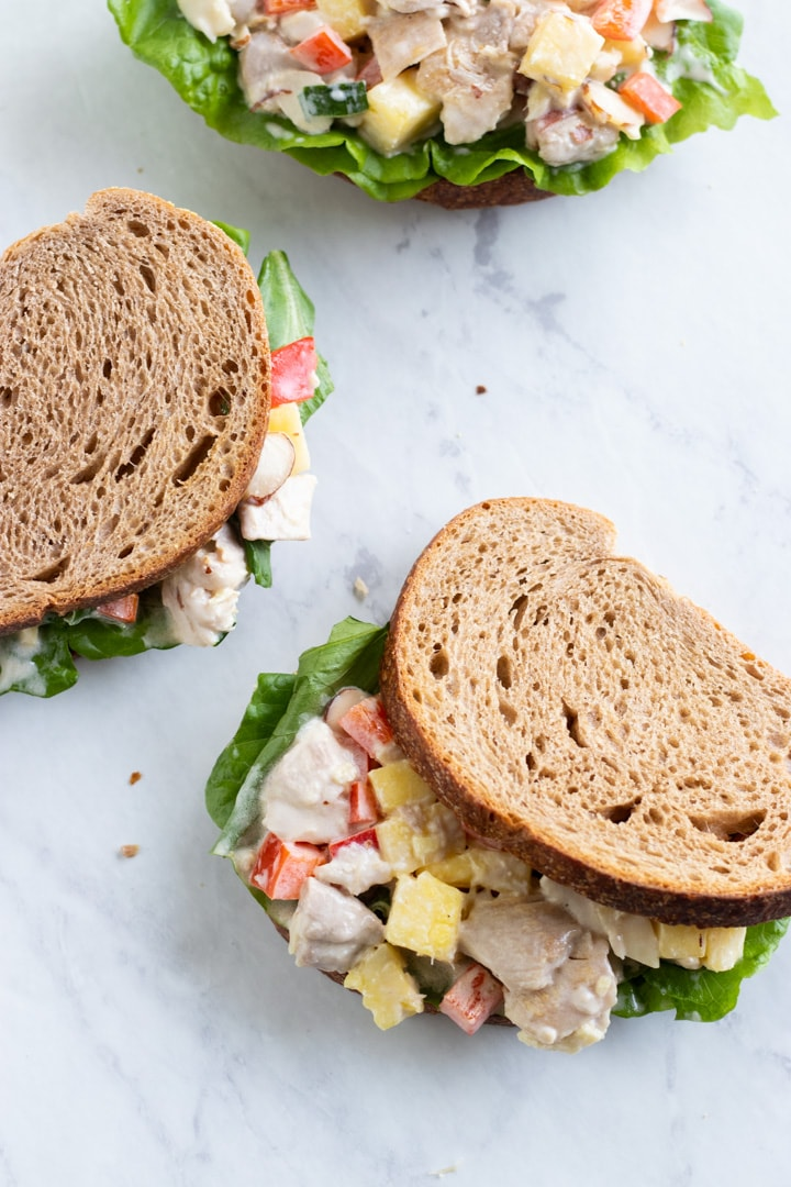 Looking down at three Hawaiinan chicken salad sandwiches sitting on a white marble counter.