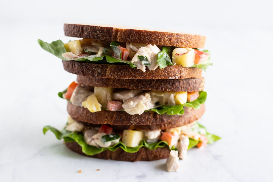 A stack of three sandwiches made with chicken, pineapple, and red bell pepper.