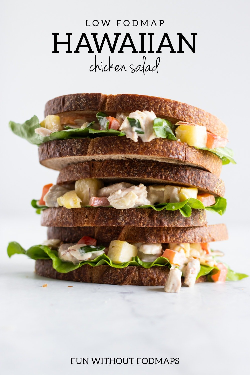 "A stack of three sandwiches made with chicken, pineapple, and red bell pepper. In the white space above, black text reads ""Low FODMAP Hawaiian Chicken Salad."""