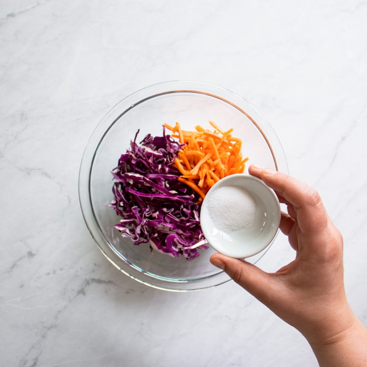 A small bowl of salt is about to be poured into a bowl of shredded red cabbage and carrots.