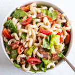 A bowl of pasta salad with a spoon.