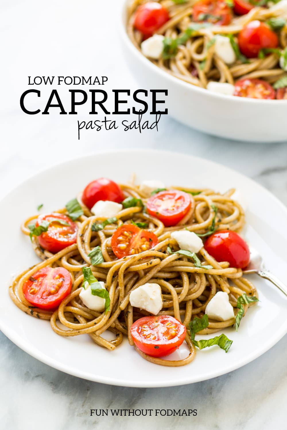 """A plate balsamic-tossed spaghetti dotted with halved cherry tomatoes, mozzarella pieces, and fresh basil. Above the plate, a black text overlay reads """"low FODMAP Caprese pasta salad."""