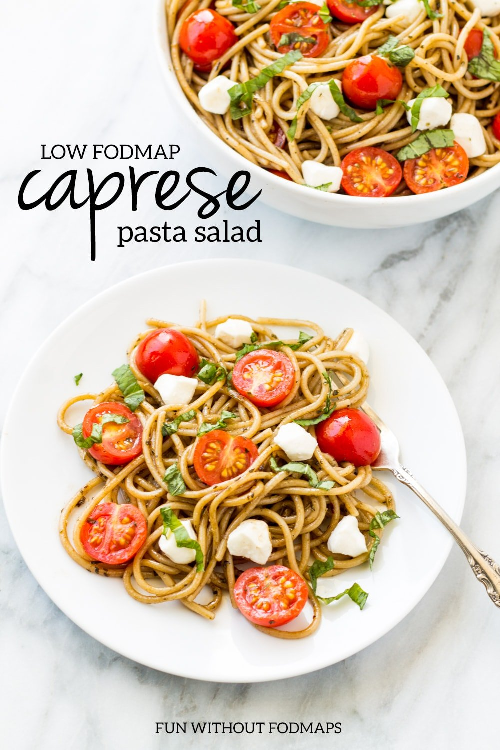 """Looking down at a plate of balsamic-tossed spaghetti dotted with halved cherry tomatoes, mozzarella pieces, and fresh basil. Above the plate, a black text overlay reads """"low FODMAP Caprese pasta salad."""