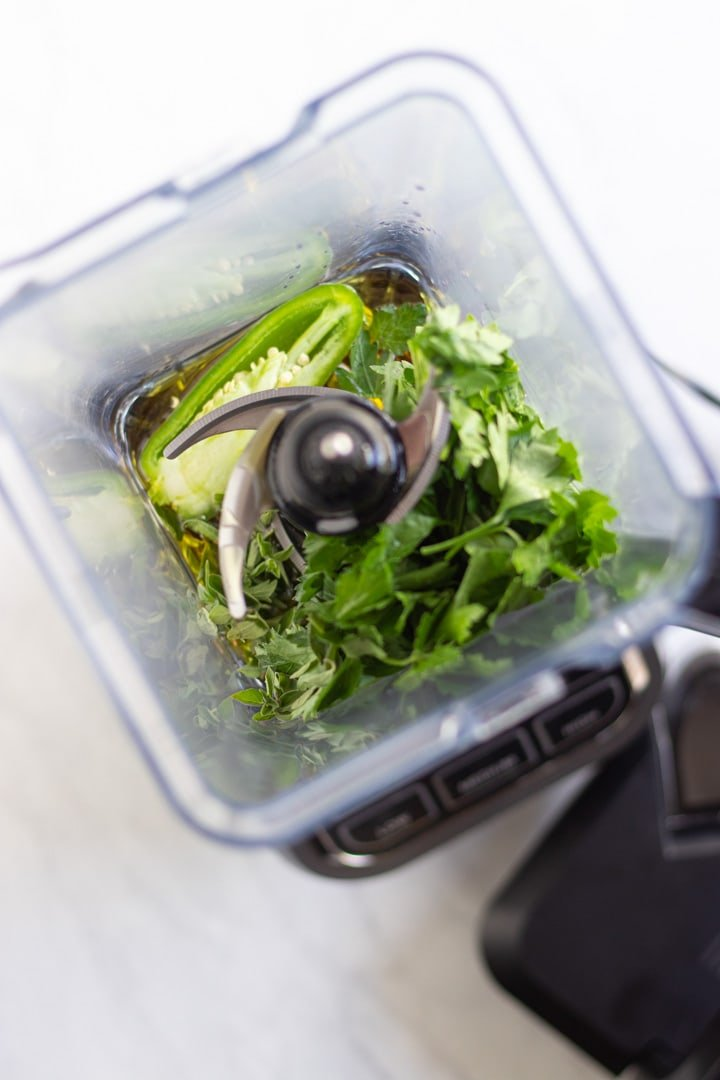 A blender filled with the ingredients needed to make low FODMAP chimichurri, including fresh parsley, jalapeno pepper, oregano, oil, and vinegar.
