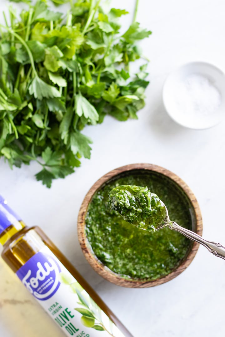 A spoonful of chimichurri is in focus over an artistically blurred bowl of the no-cook sauce. Surrounding the bowl is a bottle of low FODMAP garlic-infused oil, fresh parsley, and a pinch bowl of salt.