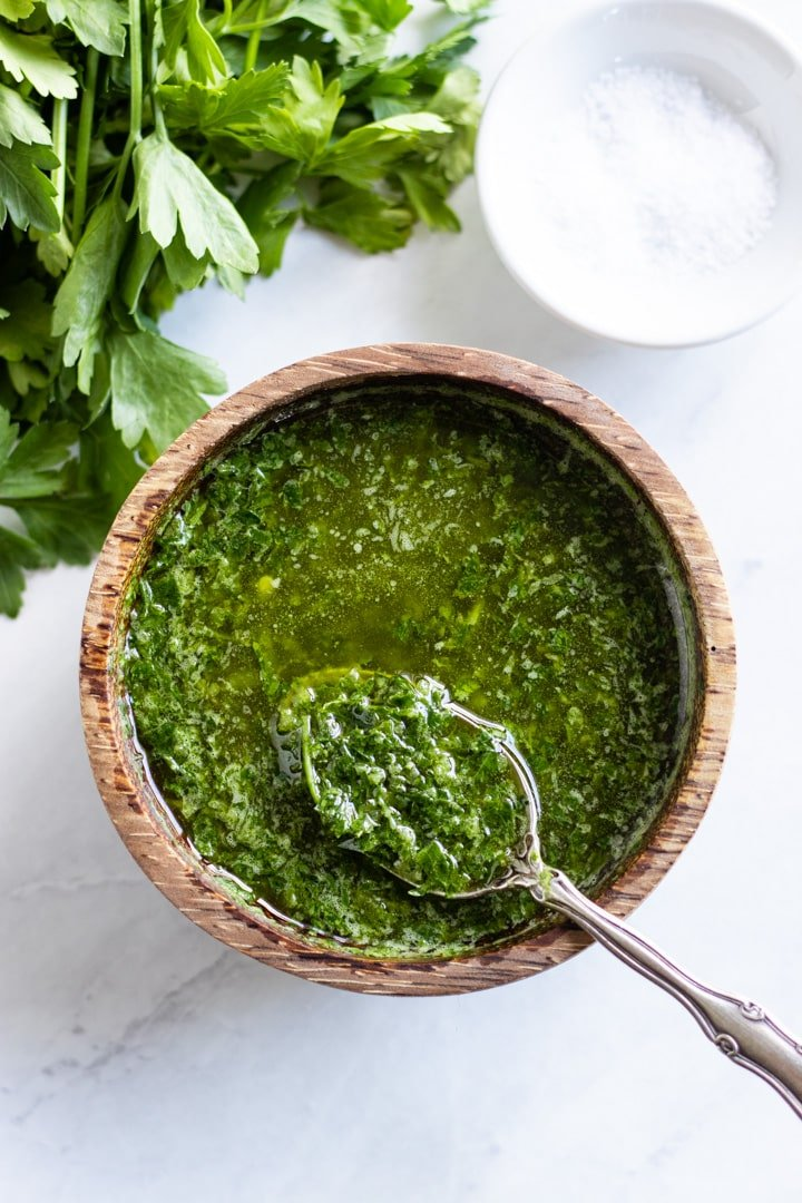 Looking down at a small wooden bowl filled with green chimichurri sauce. Fresh parsley and a pinch bowl filled with salt sit nearby.