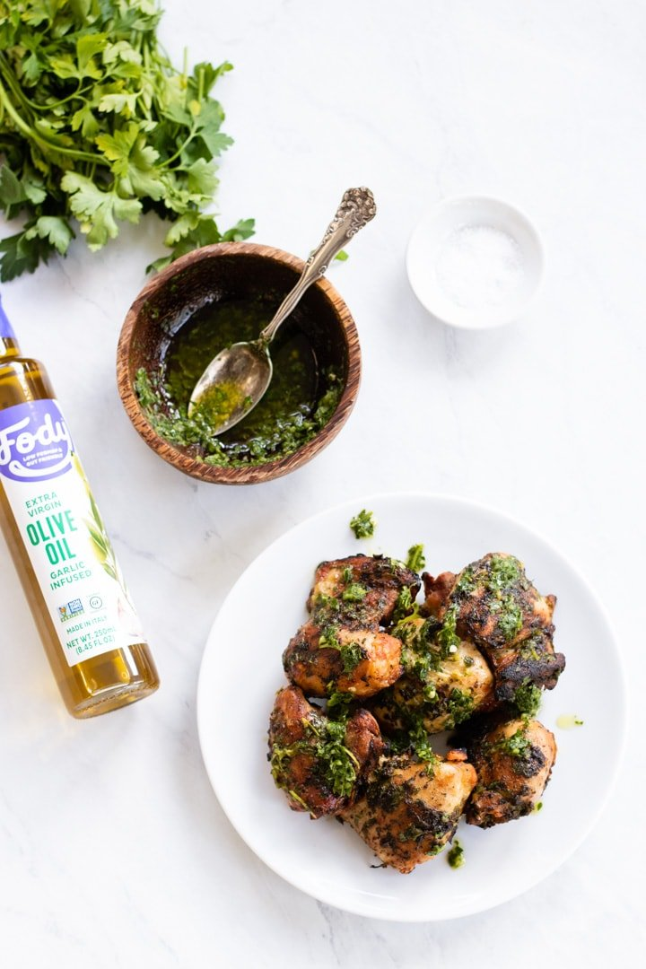 Chimichurri sauce is spooned over grilled chicken thighs.