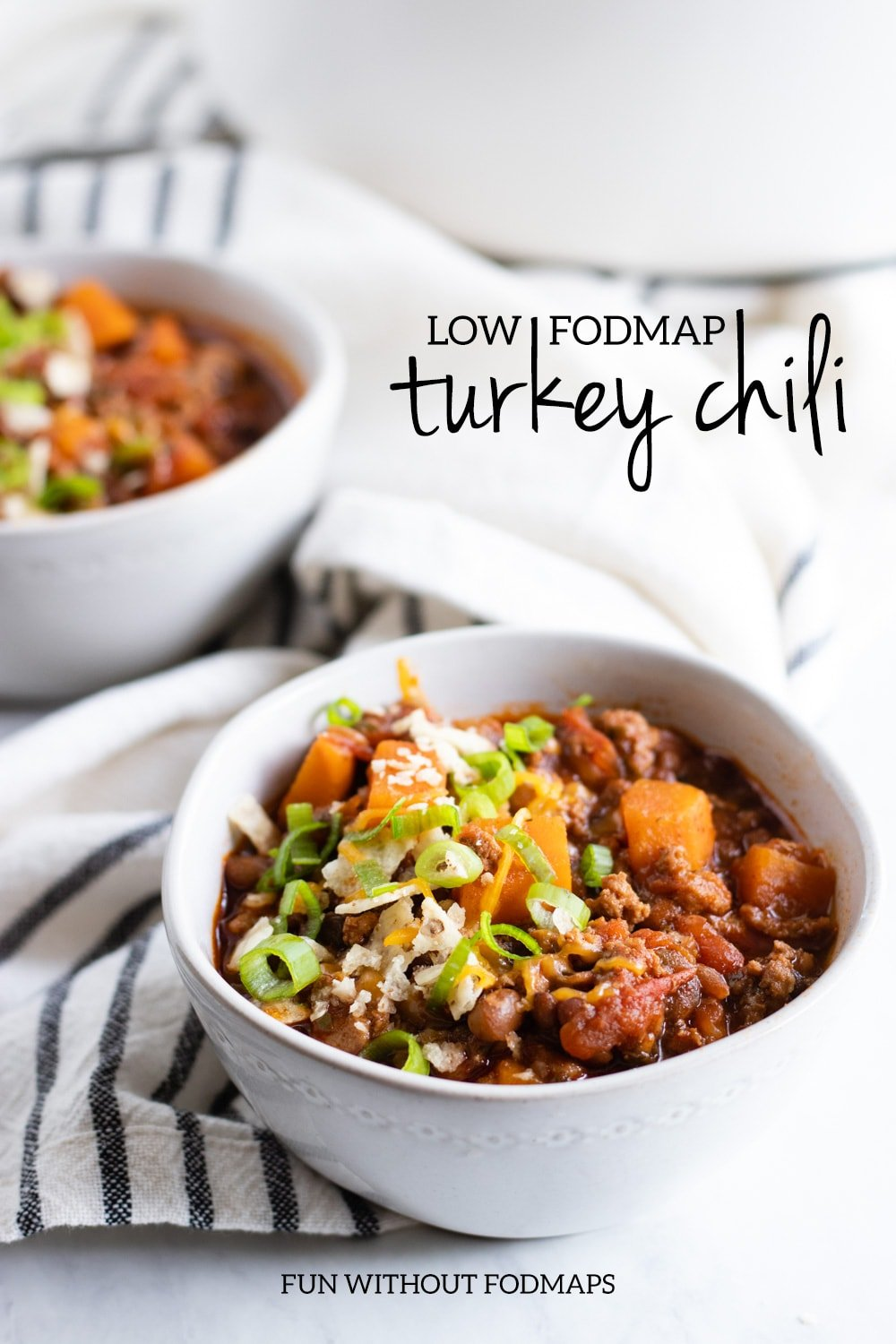 "Two bowls of chili made with ground turkey, sweet potatoes, and canned lentils sit on a white marble counter with a navy striped linen napkin in between. In the white space, black text reads ""Low FODMAP Turkey Chili."""