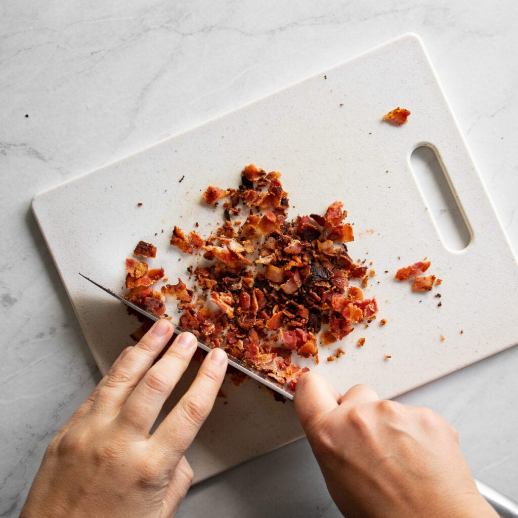 crispy bacon being sliced into bite sized pieces on cutting board