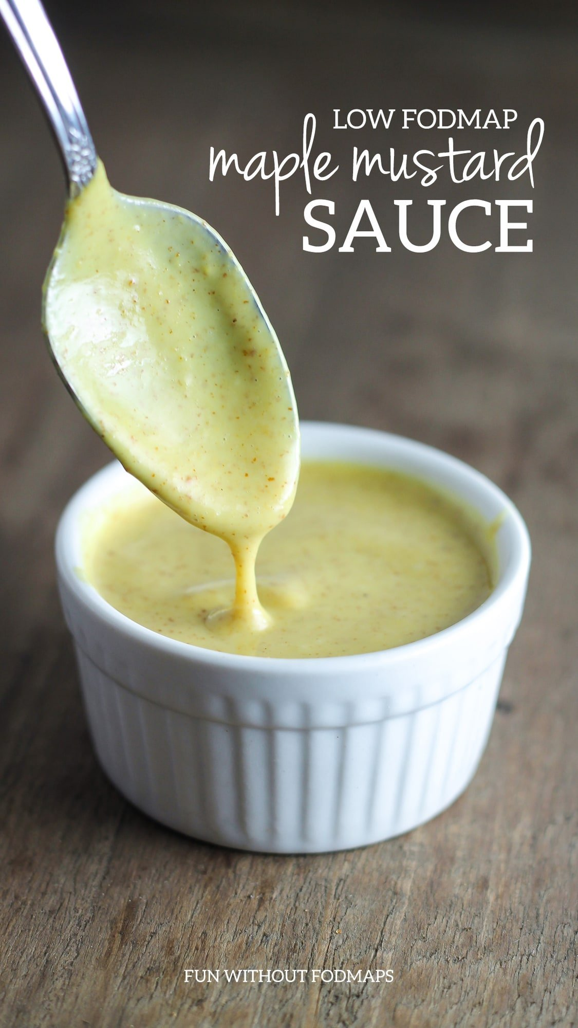 """Close up of a spoon dipped into a small container of creamy mustard. White text reads """"low FODMAP creamy maple mustard"""" and """"Fun Without FODMAPs"""""""