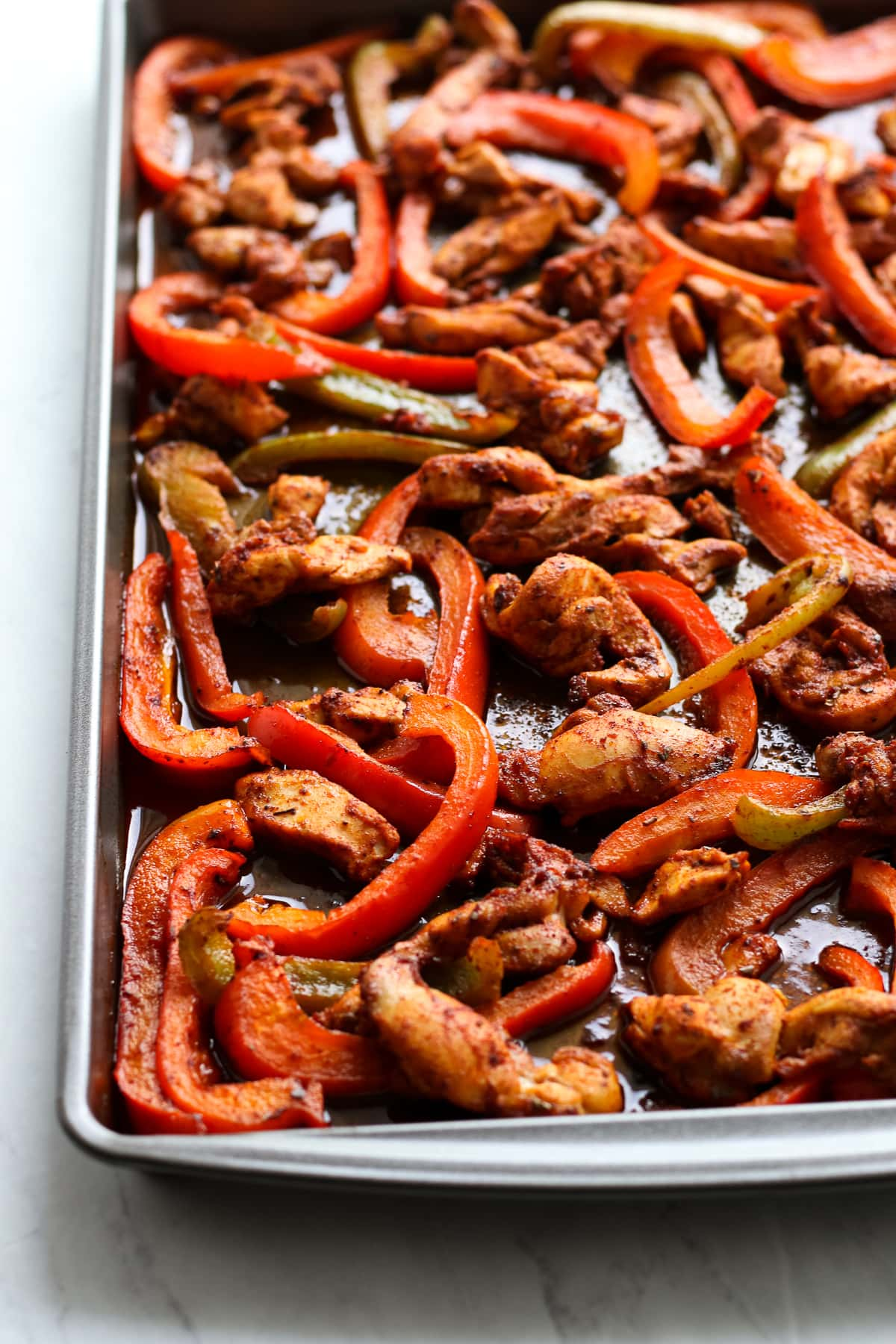 A sheet pan filled with baked chicken thigh slices and sliced red and green bell peppers.