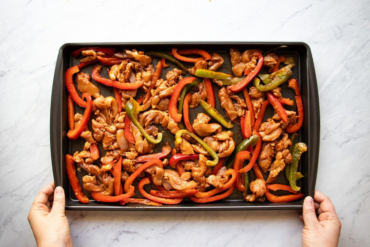 Prepared chicken fajitas spread evenly onto a baking sheet.