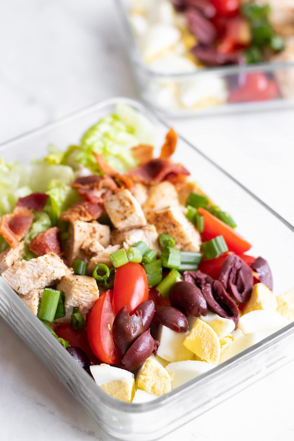 A clear reusable glass container filled with Low FODMAP Cobb Salad.