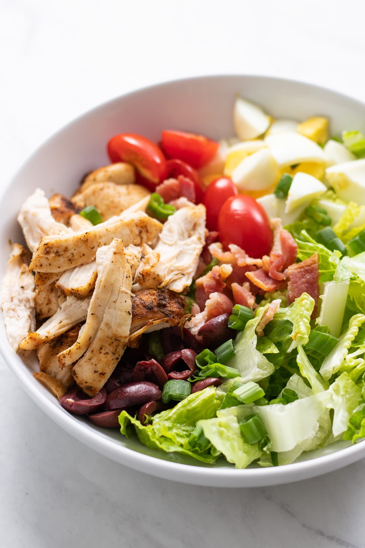 A close up of Low FODMAP Cobb Salad made with crispy romaine, broiled seasoned chicken, bacon crumbles, diced hard-boiled eggs, cherry tomatoes, and olives.