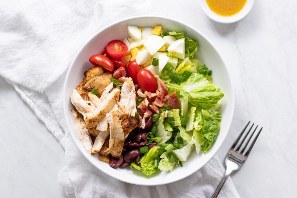 A bowl of Cobb salad sitting on a white linen napkin with a fork and small bowl of dressing on the side.
