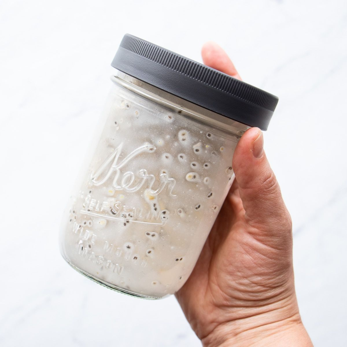 A mason jar sealed with a leakproof lid and filled with the overnight oats ingredients is about to be shaken