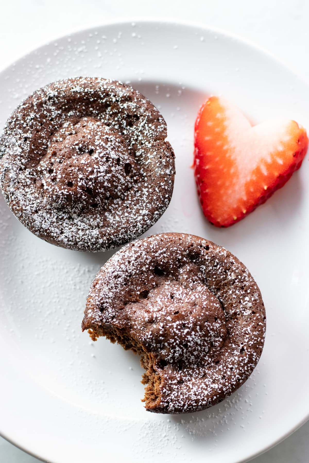 Two mini chocolate cakes on a plate with a heart-shaped strawberry slice.