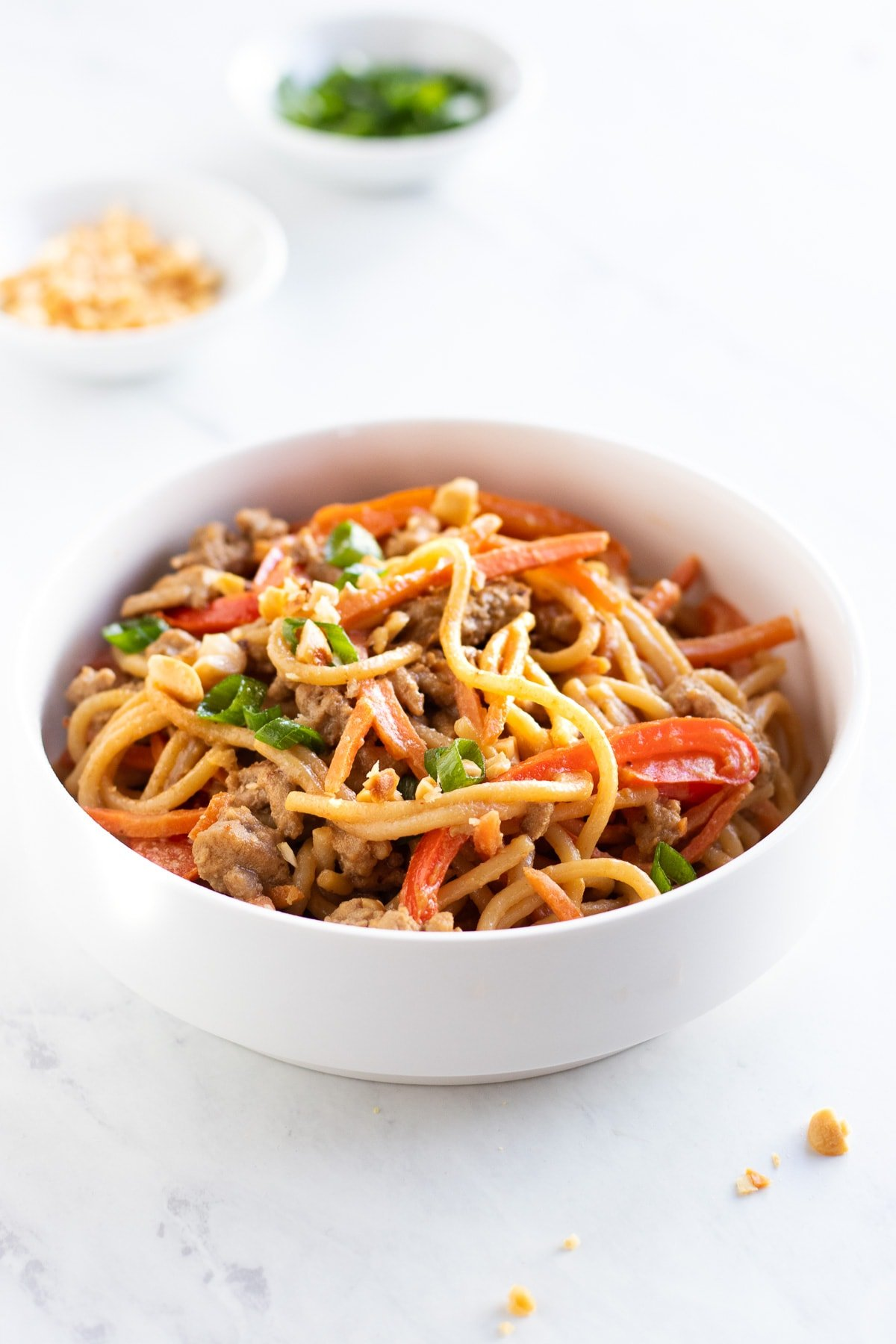A bowl of noodles coated with peanut sauce.