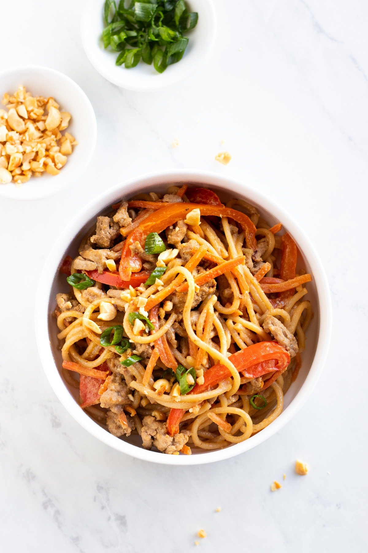 Looking down at a bowl of noodles coated with a light peanut sauce and mixed with carrot matchsticks, red pepper slices, and ground turkey.