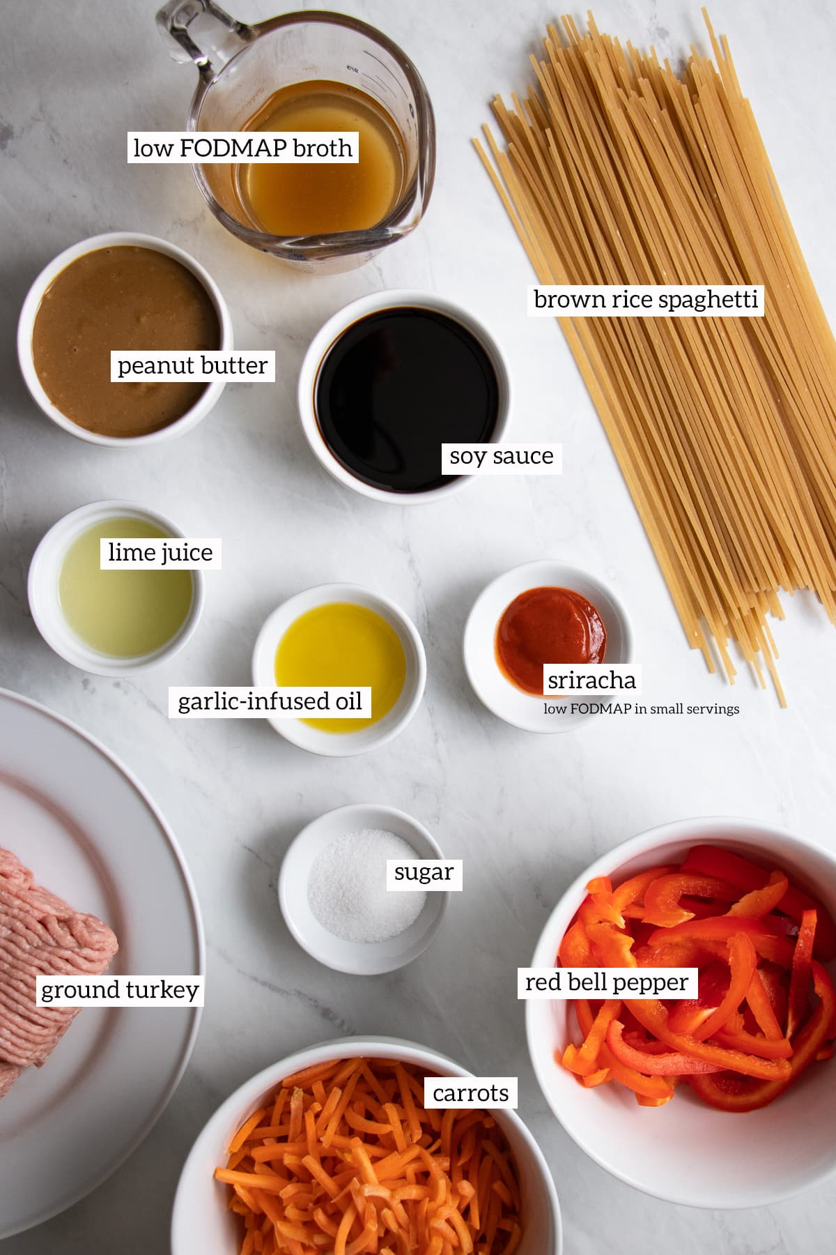 Ingredients needed for low FODMAP Thai peanut noodles are measured out into individual white dishes.