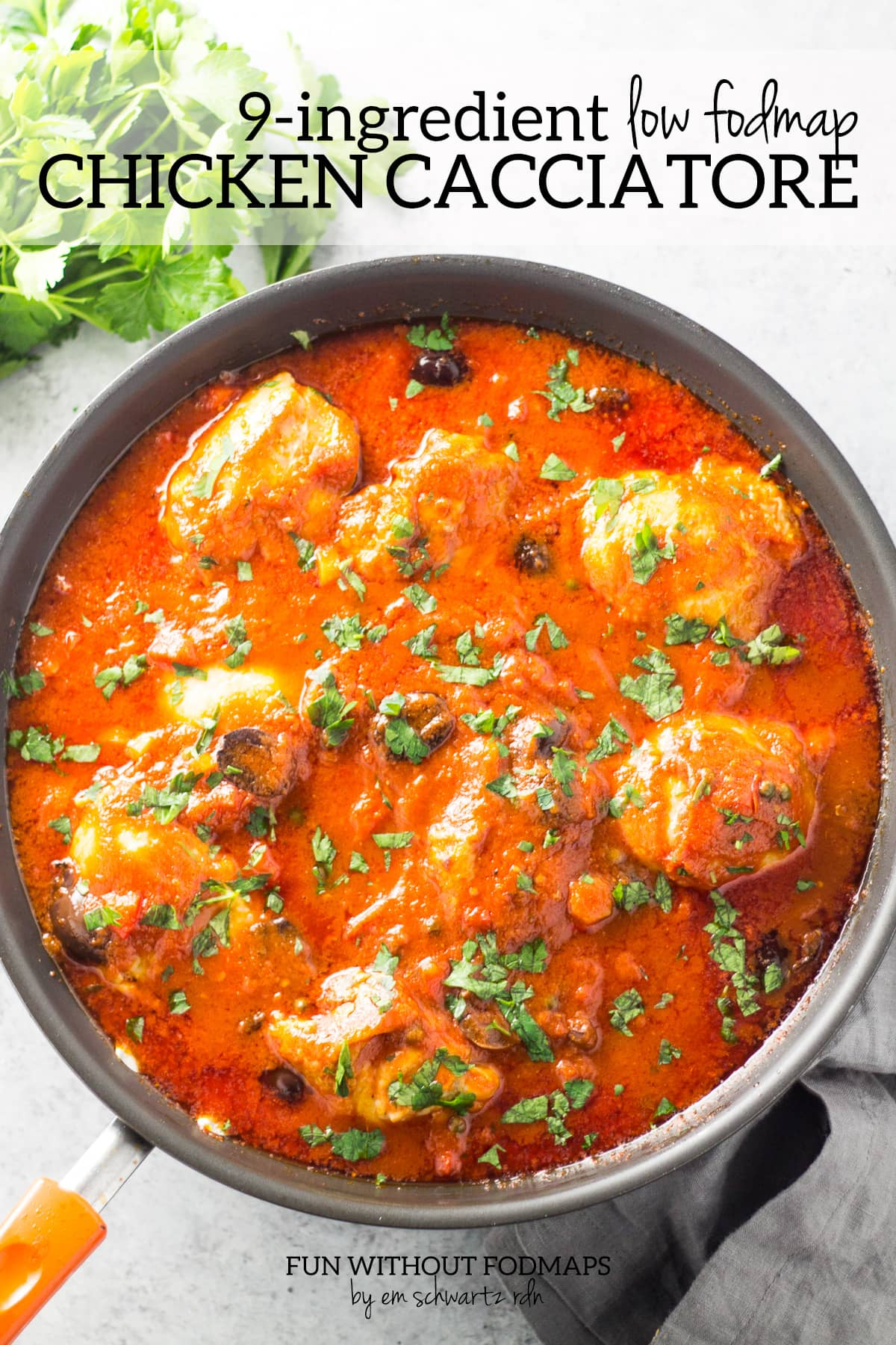 """Looking down at a skillet filled with chicken simmered in a tomato sauce. Above black text reads """"9 Ingredient Low FODMAP Chicken Cacciatore"""""""