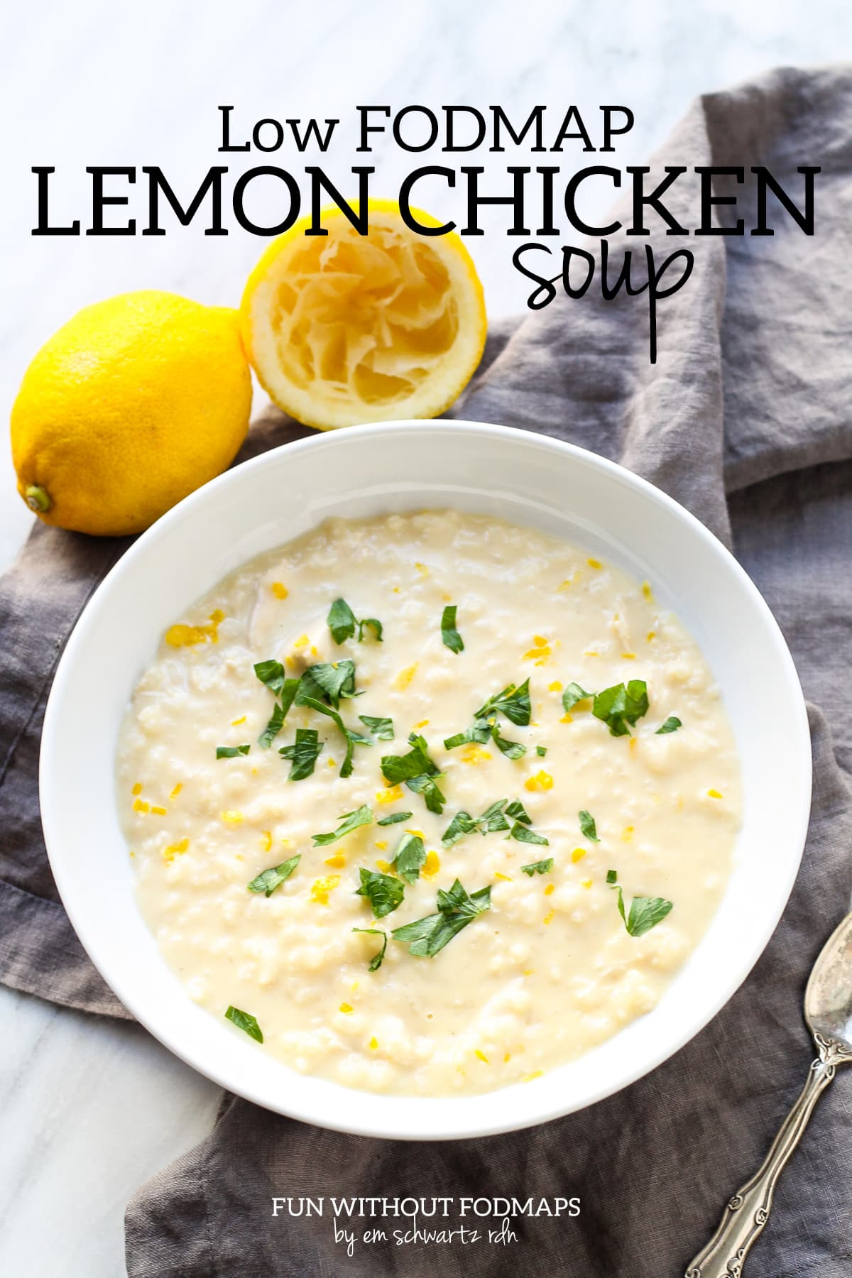 """Looking down at a bowl of lemony chicken and rice soup topped with fresh parsley and lemon zest. Above the soup, a black text overlay reads """"Low FODMAP Lemon Chicken Soup."""""""