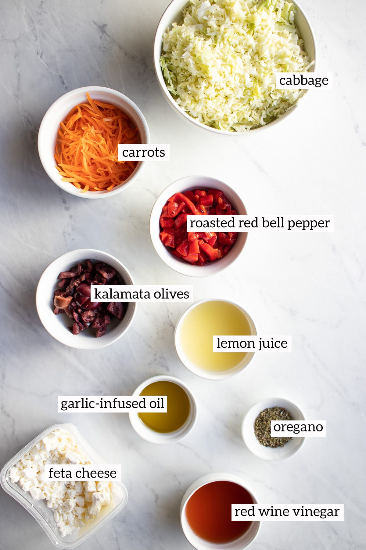 Ingredients needed for this coleslaw recipe have been measured out and placed in small white bowls.