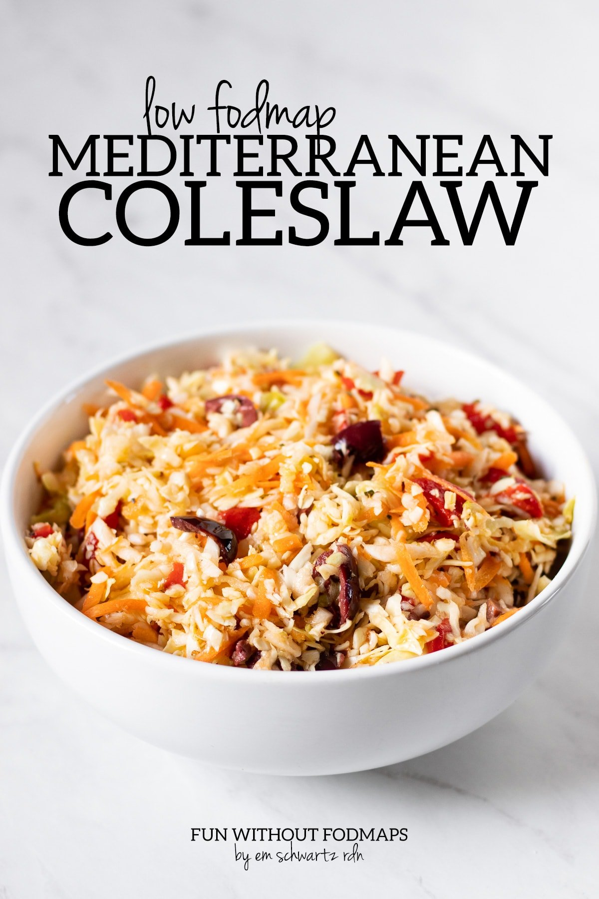 "A bowl of coleslaw made with cabbage, carrots, Kalamata olives, and roasted red peppers sit on a white marble slab. In the white space above the bowl, black text reads ""Low FODMAP Mediterranean Coleslaw."""