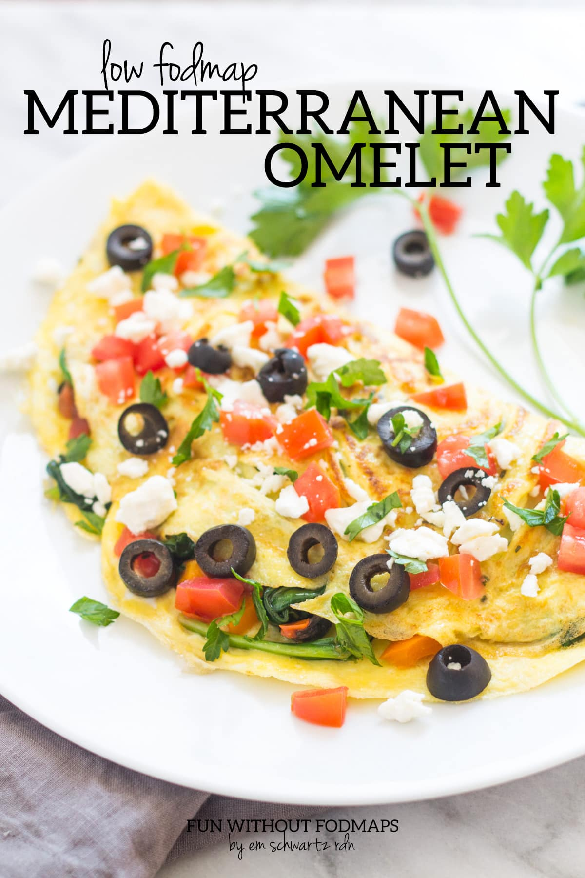 "An omelet topped with black olives, tomatoes, feta cheese, and parsley. Above black text reads ""Low FODMAP Mediterranean Omelet."""